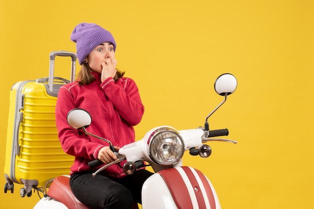 Vooraanzicht verbaasde jonge vrouw op bromfiets met gele koffer