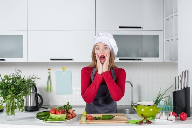 Vooraanzicht verbaasde vrouwelijke kok in schort die in keuken staat