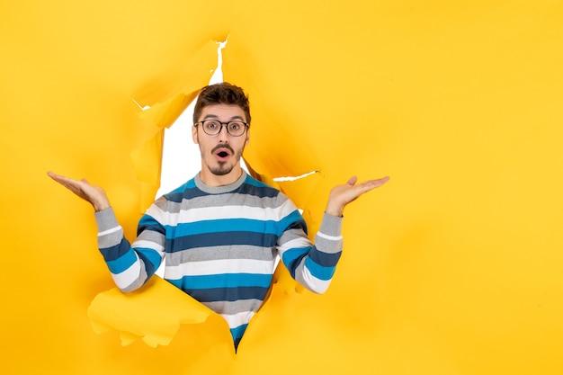 Vooraanzicht verbijsterd jonge man gluren door gat in papier gele muur