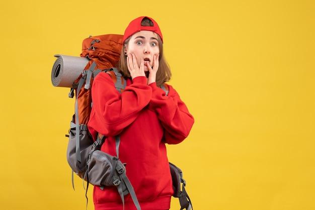 Vooraanzicht verbijsterd vrouwelijke reiziger met rugzak handen op haar gezicht zetten