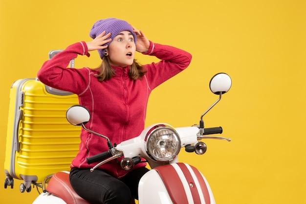 Vooraanzicht verbijsterde jonge vrouw op bromfiets met haar hoofd