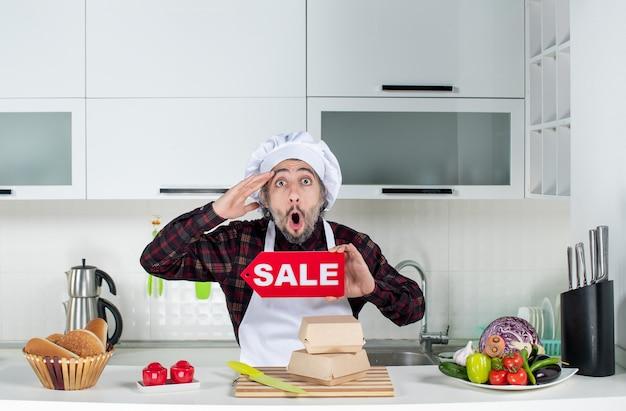 Vooraanzicht verbijsterde mannelijke chef-kok die verkoopbord in de keuken omhoog houdt