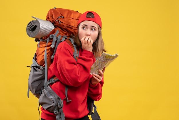 Vooraanzicht verbijsterde vrouwelijke backpacker die reiskaart bekijkt die naar iets kijkt