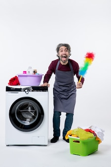 Vooraanzicht verheugde huishoudster man met stofdoek staande in de buurt van wasmachine wasmand op witte muur