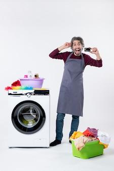 Vooraanzicht verheugde man met kaart in de buurt van wasmachine op witte muur