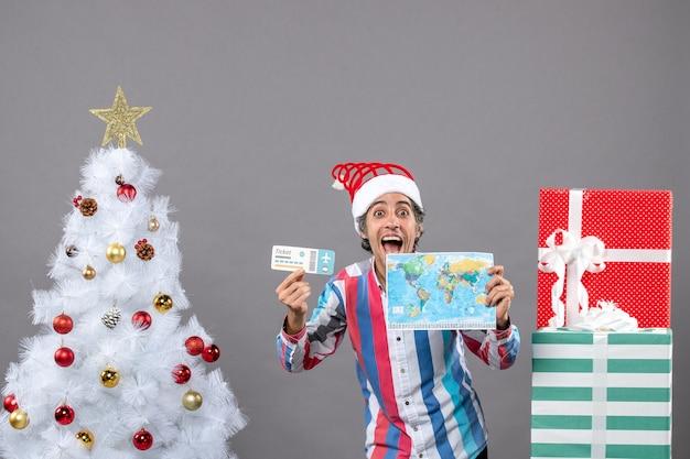 Vooraanzicht verheugde zich knappe man met spiraalvormige lente kerstmuts met wereldkaart en reisticket