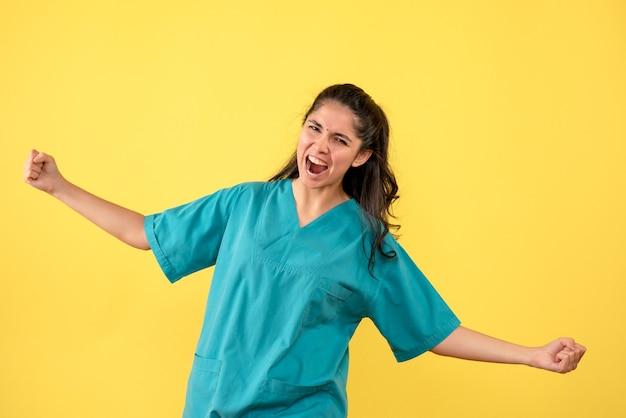 Vooraanzicht verheugde zich vrouwelijke arts die zich op gele achtergrond bevindt
