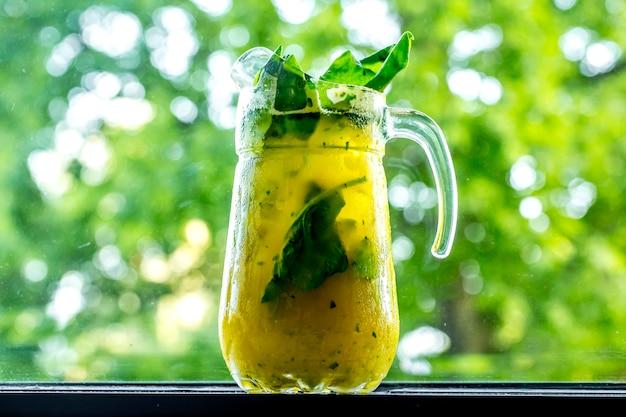 Vooraanzicht verkwikkende limonade in karaf met limoen en spinazie