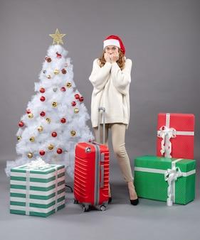 Vooraanzicht verlegen meisje met kerstmuts staande in de buurt van witte kerstboom