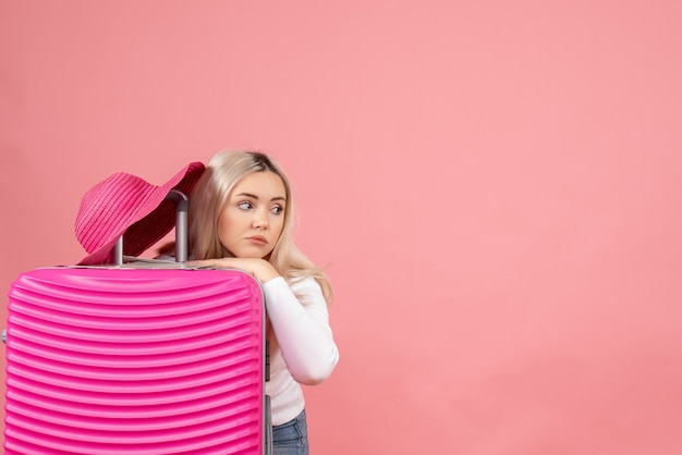Vooraanzicht vermoeide blonde vrouw met roze koffer