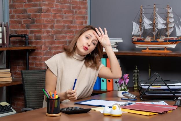 Vooraanzicht vermoeide zakenvrouw zit aan bureau