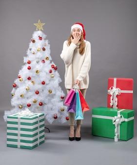 Vooraanzicht verrassende kerst meisje met kleurrijke boodschappentassen