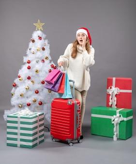 Vooraanzicht verrassende kerst vrouw met kerstmuts kerstboom geschenkdozen