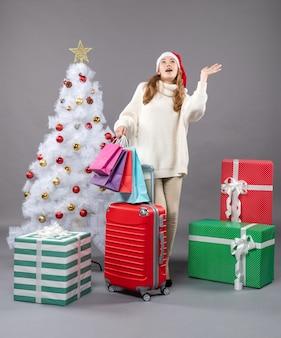 Vooraanzicht verrassende kerst vrouw met kerstmuts opzoeken