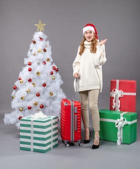 Vooraanzicht verrassende kerst vrouw met kerstmuts staande kerstboom en geschenken
