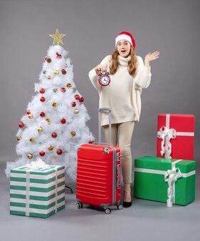 Vooraanzicht verrast blond meisje met kerstmuts met rode wekker
