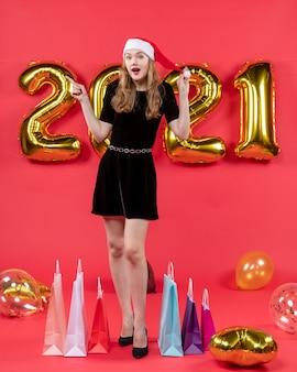 Vooraanzicht verrast jonge dame in zwarte jurk ballonnen op rood