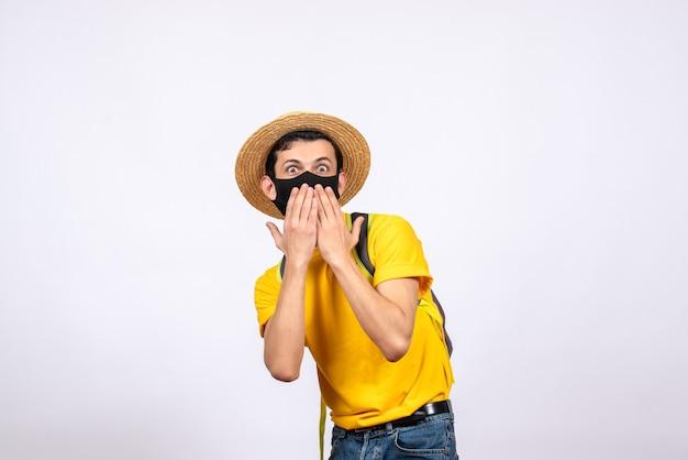 Vooraanzicht verrast jonge man met masker en geel t-shirt