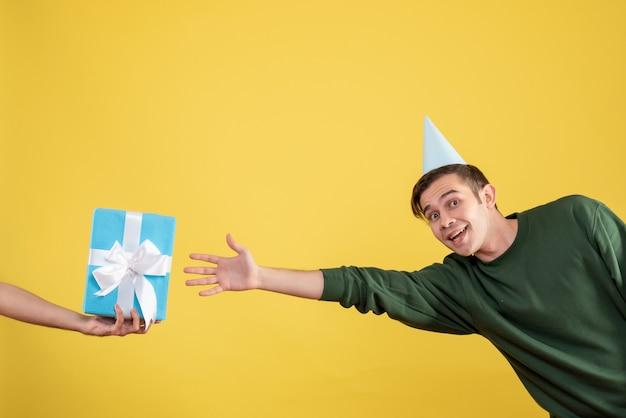 Vooraanzicht verrast jongeman met feestmuts die geschenk in menselijke hand op geel probeert te vangen