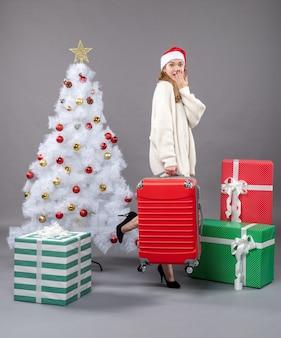 Vooraanzicht verrast kerstmismeisje die met santahoed haar rode reistas houden dichtbij kerstmisboom