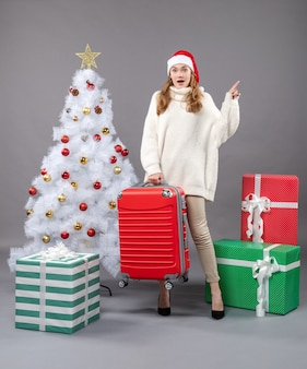 Vooraanzicht verrast kerstmismeisje die met santahoed haar rode reistas houden dichtbij witte kerstmisboom