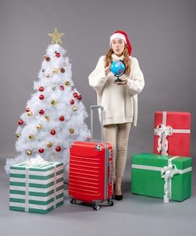 Vooraanzicht verrast kerstmismeisje met santahoed die een bol toont die zich dichtbij kerstmisboom bevindt