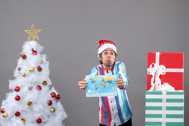 Vooraanzicht verrast man met spiraalvormige lente kerstmuts wereldkaart met beide handen te houden