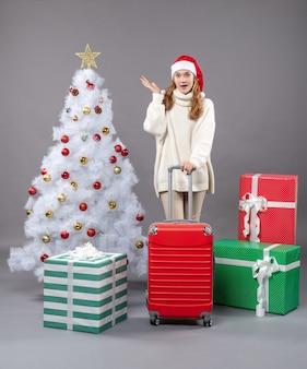 Vooraanzicht verrast meisje met kerstmuts met rode koffer staande in de buurt van kerstboom