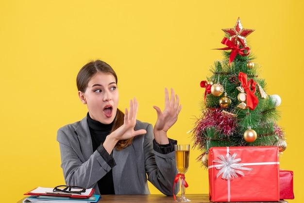 Vooraanzicht verrast meisje zit aan de balie opening handen kerstboom met speelgoed en geschenken