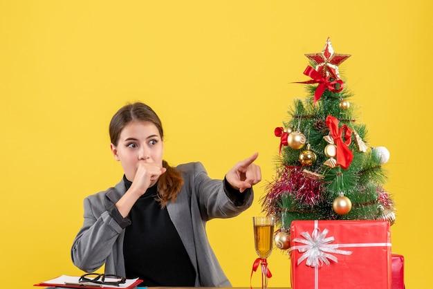 Vooraanzicht verrast meisje zittend aan het bureau wijzend met vinger iets kerstboom en geschenken cocktail