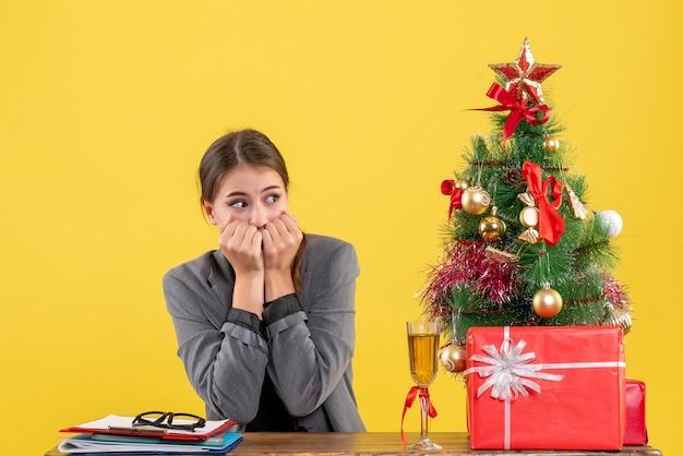 Vooraanzicht verrast schattig meisje zit aan de balie maar hand aan zijn mond kerstboom en geschenken cocktail