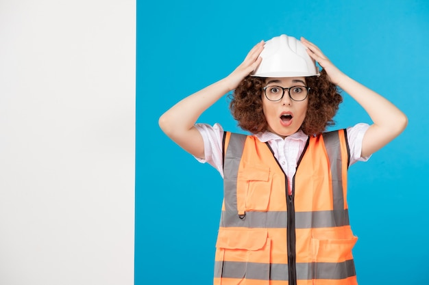 Vooraanzicht verrast vrouwelijke bouwer in uniform op blauwe muur