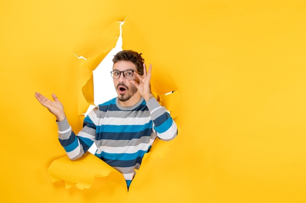 Vooraanzicht verraste jonge man die zijn bril vasthoudt en door het gat in de papieren gele muur gluurt