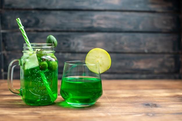 Vooraanzicht vers feijoa-sap in blik en glas op de donkere bar fruitcocktail kleur drankje foto