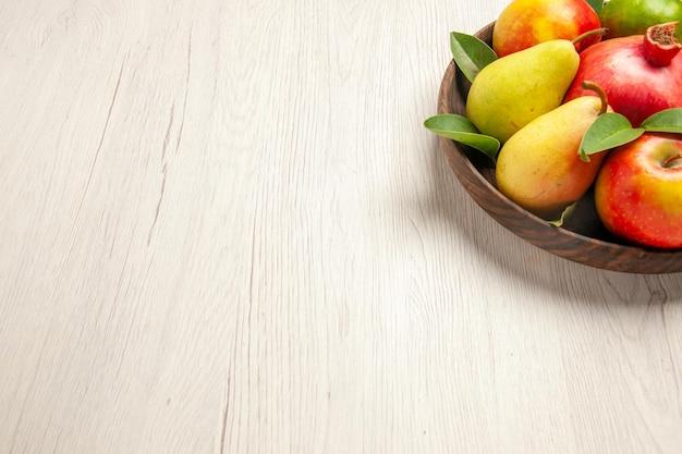Vooraanzicht vers fruit, appels, peren en ander fruit in de plaat op witte bureauvruchten, rijpe boom, zacht veel vers