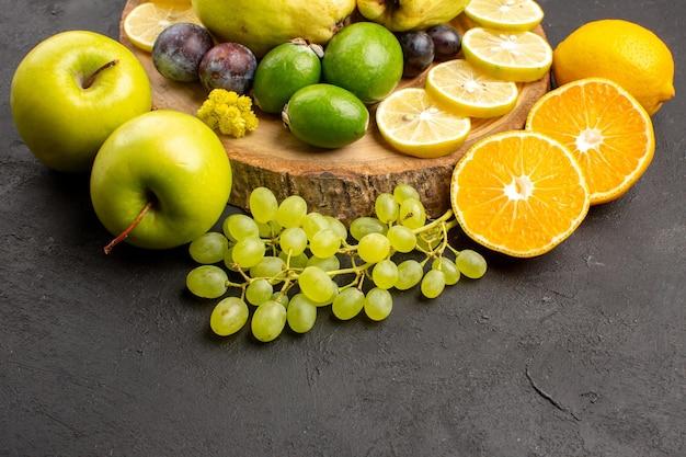 Vooraanzicht vers fruit druiven citroen schijfjes pruimen en kweeperen op donkere achtergrond rijp vers fruit plant boom