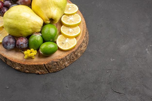 Vooraanzicht vers fruit druiven schijfjes citroen pruimen en kweeperen op de donkere achtergrond vers fruit rijpe boomplant