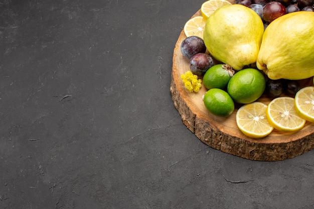 Vooraanzicht vers fruit druiven schijfjes citroen pruimen en kweeperen op de donkere achtergrond vers fruit rijpe plantenboom