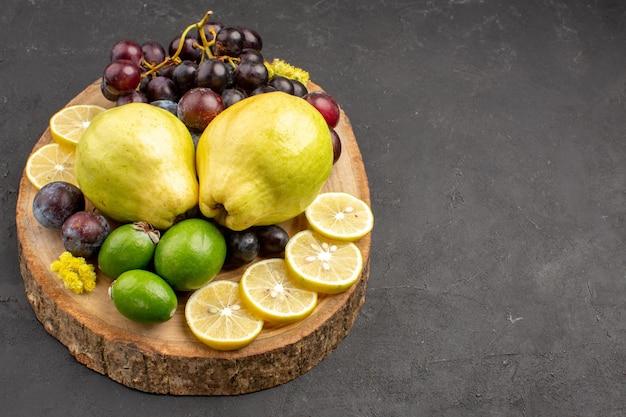 Vooraanzicht vers fruit druiven schijfjes citroen pruimen en kweeperen op de donkere achtergrond vers fruit rijpe plantenboom Gratis Foto