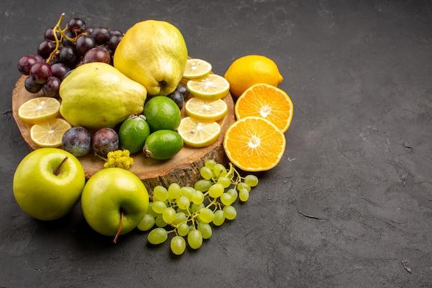 Vooraanzicht vers fruit druiven schijfjes citroen pruimen en kweeperen op donker bureau vers fruit rijpe plantenboom
