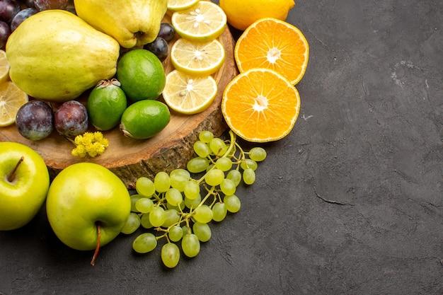 Vooraanzicht vers fruit druiven schijfjes citroen pruimen en kweeperen op donkere achtergrond rijp vers fruit gezondheid vitamine boom