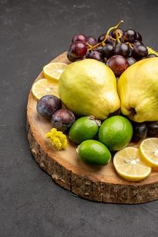 Vooraanzicht vers fruit druiven, schijfjes citroen, pruimen en kweeperen op een donker bureau, vers fruit, rijpe boomplant