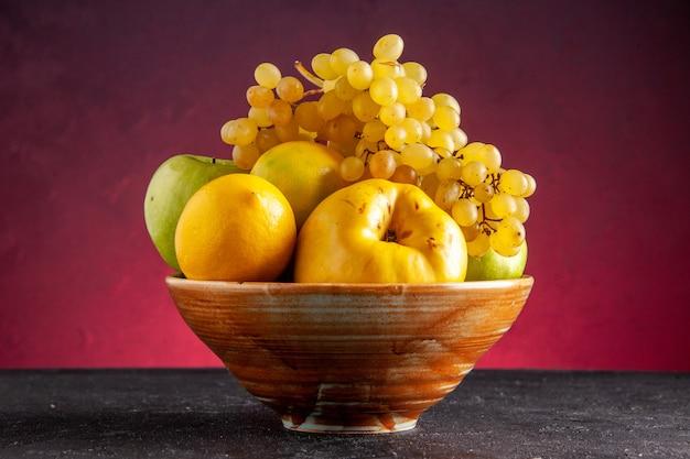 Vooraanzicht vers fruit in houten kom appels kweepeer citroen druiven op rode tafel