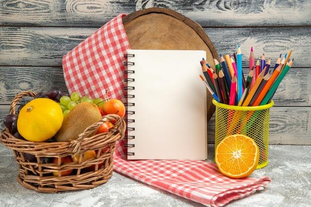 Vooraanzicht vers fruit met notitieblok en potloden op grijze achtergrond fruit citrus voorbeeldenboek kleur