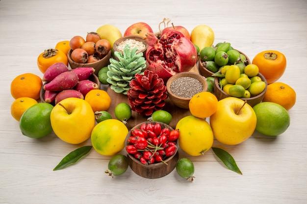 Vooraanzicht vers fruit samenstelling verschillende vruchten op witte achtergrond smakelijke gezondheid citrusboom kleur bessen dieet exotisch