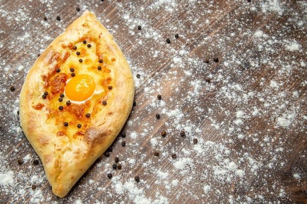 Vooraanzicht vers gebakken brood met gekookt ei en bloem op bruin bureaudeeg bak het broodje van het eierbrood