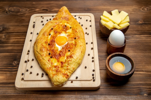 Vooraanzicht vers gebakken brood met gekookt ei op bruin het voedselontbijt van het bureldeeg bak broodjemaaltijd