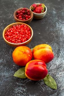 Vooraanzicht vers gepelde granaatappels met perziken op donkere tafel