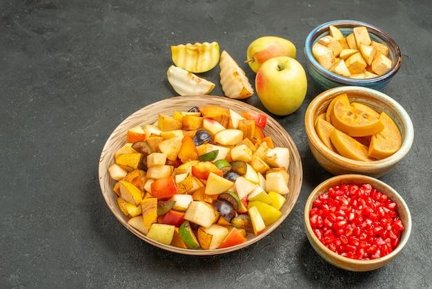 Vooraanzicht vers gesneden fruit met granaatappels op een donkergrijze tafel veel fruit gezondheid