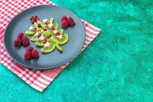 Vooraanzicht vers gesneden kiwi's met frambozen op groene oppervlaktebessen exotisch fruit foto tropische kleur